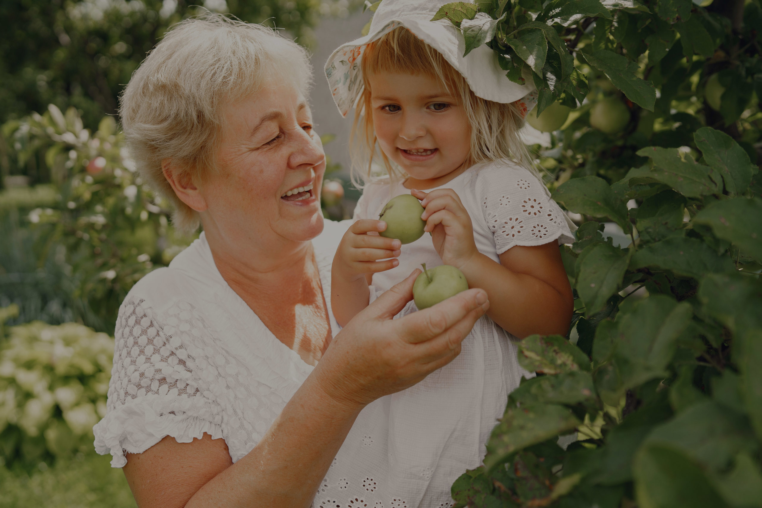 Grandmother and granddaughter together, hugging and joyfully laughing in a Flowering apricot garden in April. Family outdoors lifestyle.